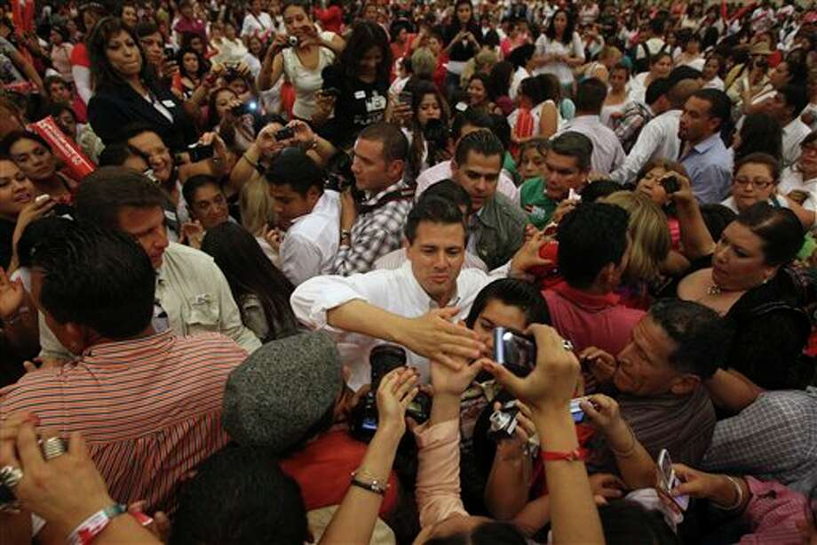 Presidential candidate Enrique Pena Nieto, of the Revolutionary Institutional Party (PRI), center, reaches out to supporters during a campaign event with women in Guadalajara, Mexico, Friday March 30, 2012.  The four candidates for Mexico's presidency officially launched their campaigns for the July 1 election on Friday, all of them promising change.  (AP Photo/Bruno Gonzalez) Photo: Bruno Gonzalez, Associated Press / AP