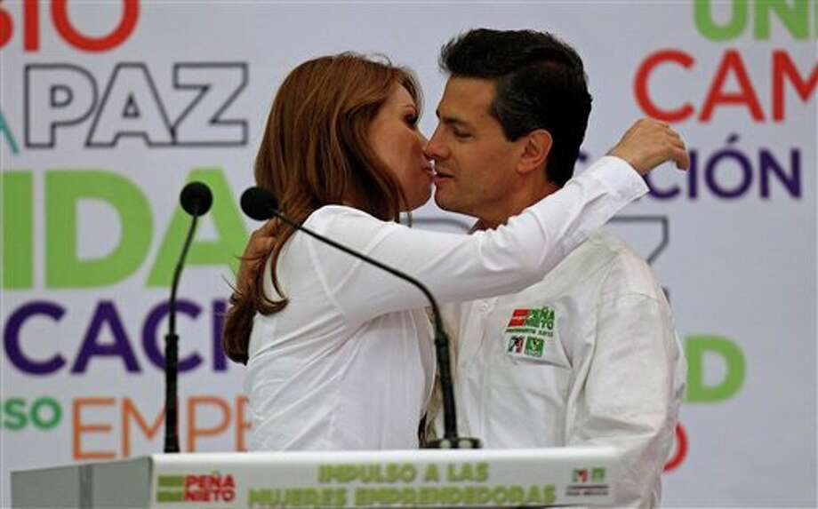 Presidential candidate Enrique Pena Nieto, of the Revolutionary Institutional Party (PRI), right, reaches to kiss his wife Angelica Rivero during a campaign event with women in Guadalajara, Mexico, Friday March 30, 2012. The four candidates for Mexico's presidency officially launched their campaigns for the July 1 election on Friday, all of them promising change.  (AP Photo/Bruno Gonzalez) Photo: Bruno Gonzalez, Associated Press / AP