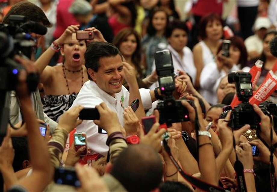 Presidential candidate Enrique Pena Nieto, of the Revolutionary Institutional Party (PRI), greets supporters during a campaign event with women in Guadalajara, Mexico, Friday March 30, 2012. The four candidates for Mexico's presidency officially launched their campaigns for the July 1 election on Friday, all of them promising change.  (AP Photo/Bruno Gonzalez) Photo: Bruno Gonzalez, Associated Press / AP
