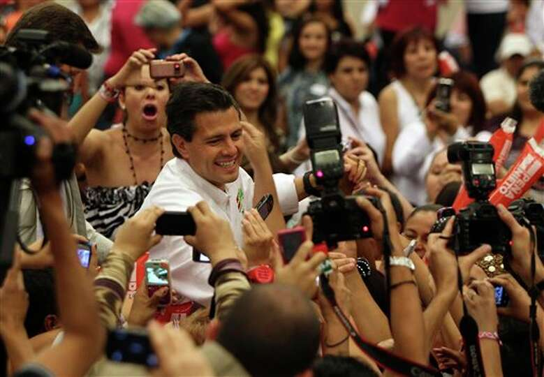 Presidential candidate Enrique Pena Nieto, of the Revolutionary Institutional Party (PRI), greets su