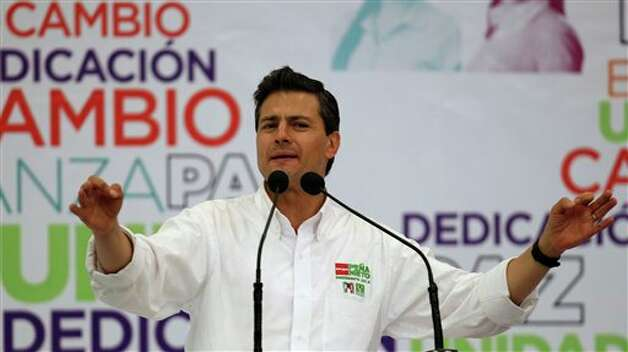 "Presidential candidate Enrique Pena Nieto, of the Revolutionary Institutional Party (PRI), speaks during a campaign event with women in Guadalajara, Mexico, Friday March 30, 2012. The four candidates for Mexico's presidency officially launched their campaigns for the July 1 election on Friday, all of them promising change. The word on the sign behind him at top left reads in Spanish ""Change."" (AP Photo/Bruno Gonzalez) Photo: Bruno Gonzalez, Associated Press / AP"
