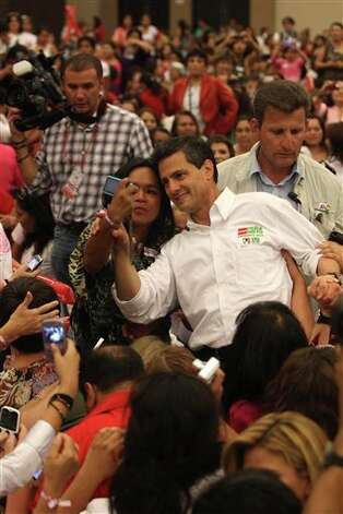 Presidential candidate Enrique Pena Nieto, of the Revolutionary Institutional Party (PRI), poses for a photo with a woman during a campaign event with women in Guadalajara, Mexico, Friday March 30, 2012. The four candidates for Mexico's presidency officially launched their campaigns for the July 1 election on Friday, all of them promising change.  (AP Photo/Bruno Gonzalez) Photo: Bruno Gonzalez, Associated Press / AP