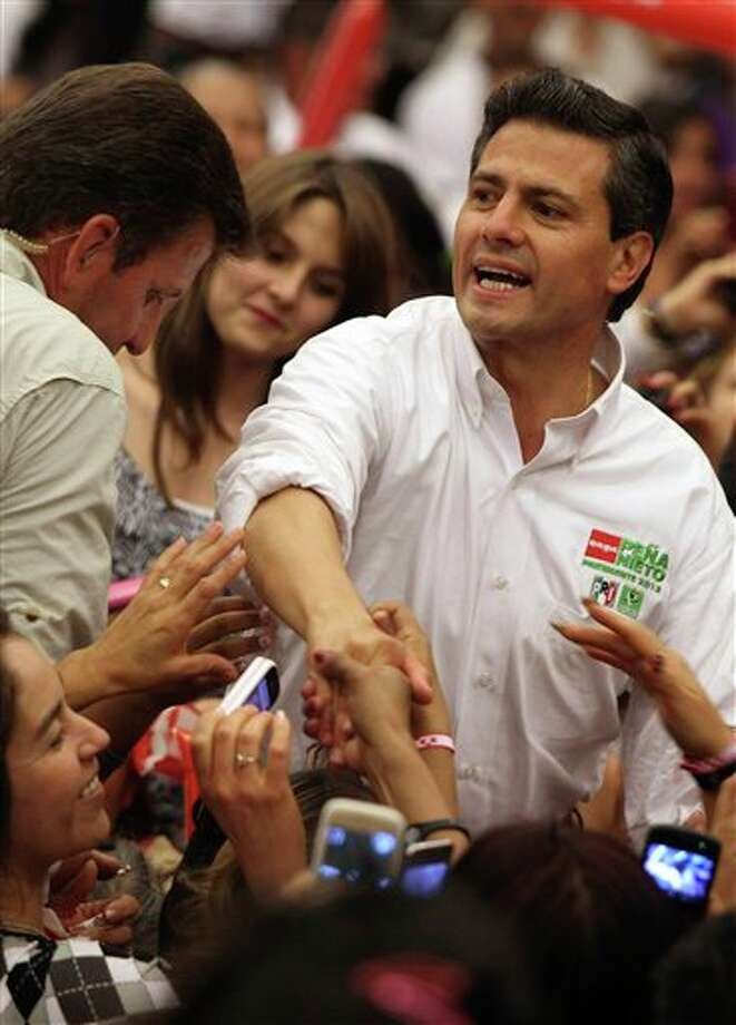 Presidential candidate Enrique Pena Nieto, of the Revolutionary Institutional Party (PRI), reaches out to supporters during a campaign event with women in Guadalajara, Mexico, Friday March 30, 2012. The four candidates for Mexico's presidency officially launched their campaigns for the July 1 election on Friday, all of them promising change.  (AP Photo/Bruno Gonzalez) Photo: Bruno Gonzalez, Associated Press / AP