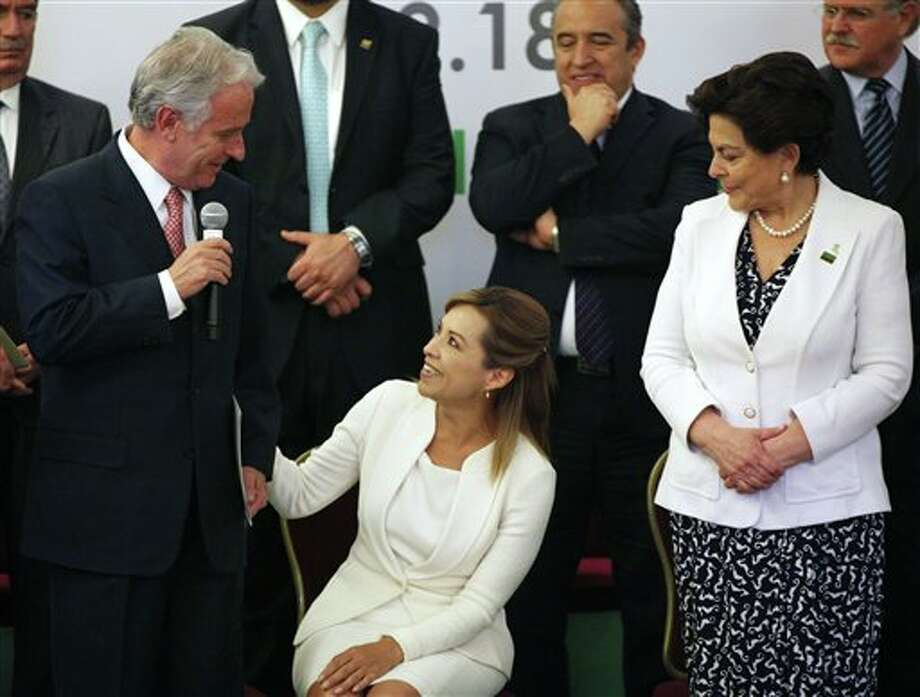 Josefina Vazquez Mota, presidential candidate for the now-governing National Action Party, PAN, center, and  Mexican businessman Alejandro Marti, left, speak during an event organized by Civil Society Mexico SOS to deliver a document about justice and security, in Mexico City, Monday, April 2, 2012. The four candidates for Mexico's presidency officially launched their campaigns for the July 1 election on Friday, all of them promising change. (AP Photo/Alexandre Meneghini) Photo: Alexandre Meneghini, Associated Press / AP