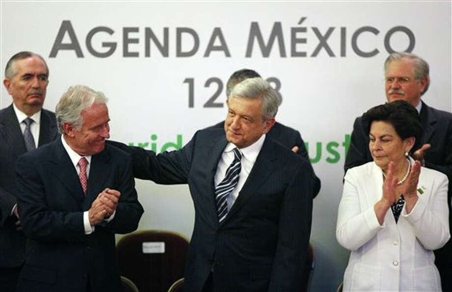 Andres Manuel Lopez Obrado, presidential candidate of the Democratic Revolution Party, PRD, center, and Mexican businessman Alejandro Marti, left front, during an event hosted by the non-governmental organization Mexico SOS, that advocates security and justice, in Mexico City, Monday April 2, 2012. The four candidates for Mexico's presidency officially launched their campaigns for the July 1 election on Friday, all of them promising change. (AP Photo/Alexandre Meneghini) Photo: Alexandre Meneghini, Associated Press / AP