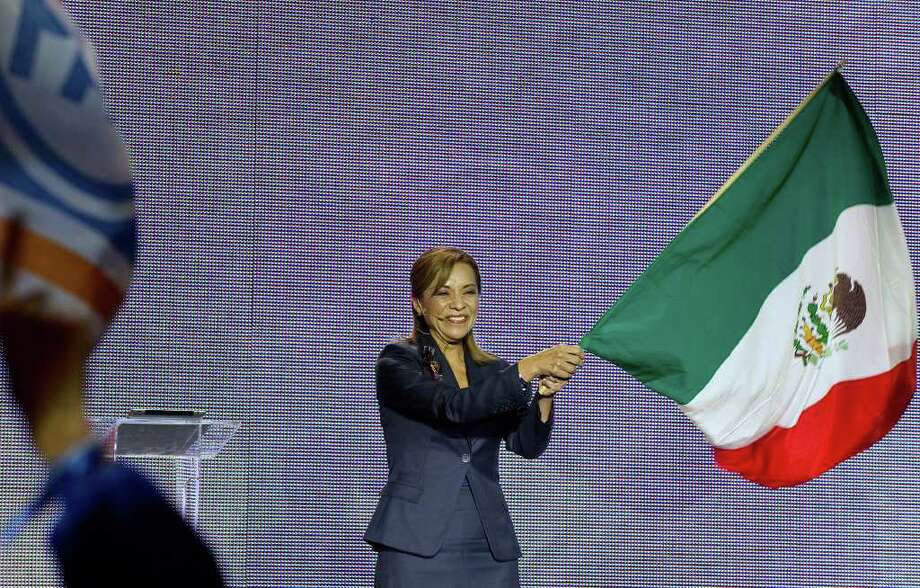 Mexican presidential candidate Josefina Vazquez Mota waves a Mexican flag during the opening her campaign for the July 1 presidential elections in Mexico City on March 30, 2012.  Mota, a 51-year-old economist and former minister, is Mexico's ruling conservative party candidate for presidential elections becoming the first female to stand for president from one of the three main parties.  AFP PHOTO/Alfredo Estrella Photo: ALFREDO ESTRELLA, Getty Images / 2012 AFP
