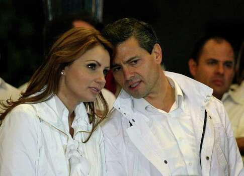 Mexican presidential candidate Enrique Pena Nieto (R) from the Institutional Revolutionary Party (PRI), speaks with his wife Angelica Rivera during the start of his presidential campaign, at Guadalajara square esplanade in Guadalajara, state of Jalisco, early on March 30, 2012. Mexico will hold presidential elections next July 1, 2012.   AFP PHOTO/Hector Guerrero Photo: HECTOR GUERRERO, Getty Images / 2012 AFP
