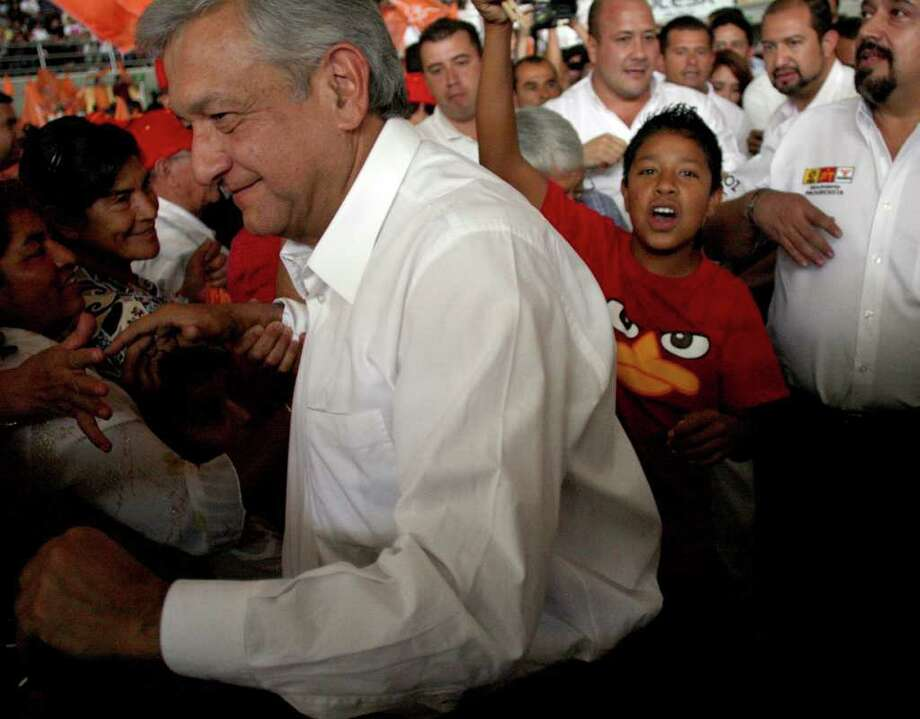 A child cheers as Mexican presidential candidate of the leftist coalition Progressive Movement of Mexico, Andres Manuel Lopez Obrador (L), arrives at a massive event of his electoral campaign, in Tlajomulco, state of Jalisco, on March 31, 2012. Mexico will hold presidential elections next July 1, 2012. AFP PHOTO/Hector Guerrero Photo: HECTOR GUERRERO, Getty Images / 2012 AFP