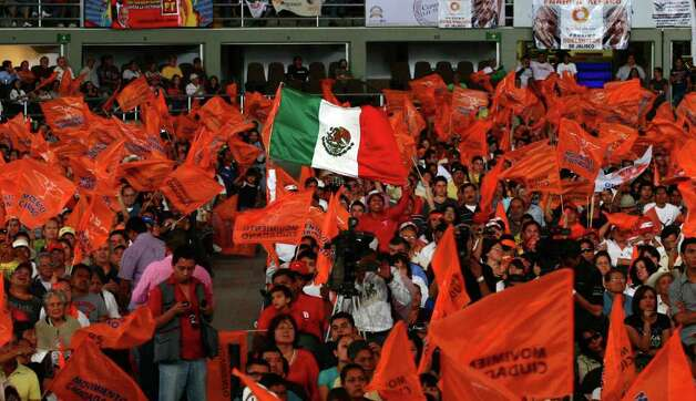 Supporters of mexican presidential candidate of the leftist coalition Progressive Movement of Mexico, Andres Manuel Lopez Obrador, cheer with flags during a massive event of his electoral campaign, in Tlajomulco, state of Jalisco, on March 31, 2012. Mexico will hold presidential elections next July 1, 2012.   AFP PHOTO/Hector Guerrero Photo: HECTOR GUERRERO, Getty Images / 2012 AFP