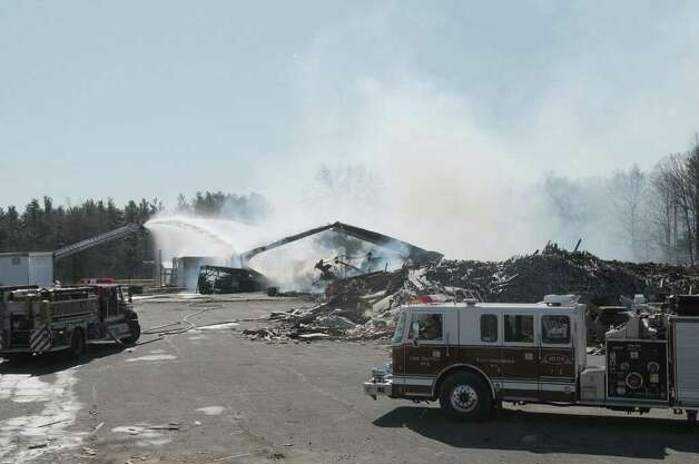 Firefighters work the scene of a fire at  Excelsior Inc. Tuesday morning, April 3, 2012 in Schodack, NY.  The building houses a business that manufactures firestarting bricks, using wood chips and sawdust to manufacture the bricks.  (Paul Buckowski / Times Union) Photo: Paul Buckowski
