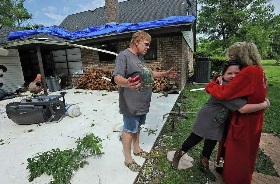 Darlene LaFleur, left, is hugged by Sierra Hutchison, 10, after LaFleur's  Orangefield home was damaged by Monday morning's straight line winds. Becky Hutchison is also pictured. The National Weather Service said no tornadoes were reported in the area. Photo taken Monday, April 2, 2012 Guiseppe Barranco/The Enterprise Photo: Guiseppe Barranco, STAFF PHOTOGRAPHER / The Beaumont Enterprise