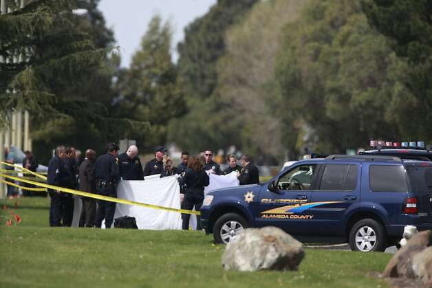 Officials hold up tarps and surround the bodies of victims from the shootings at Oikos University before they are removed form Edgewater Road on Monday, April 2, 2012 in Oakland, Calif. Authorities have confirmed that seven people have been killed by a gunman at a Oikos University in Oakland. Photo: Lea Suzuki, The Chronicle