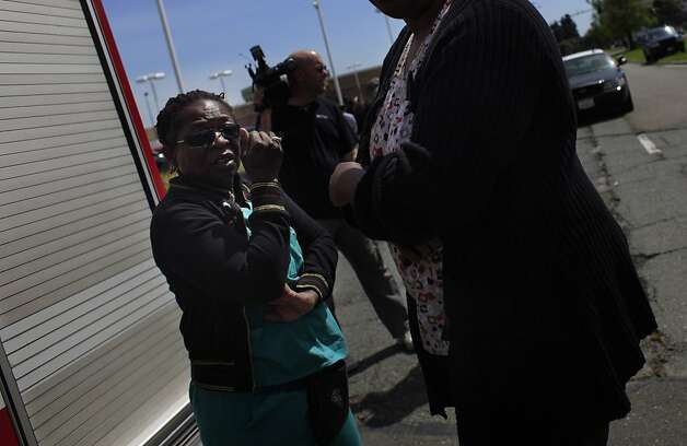 Marilyn Daniels (left) who works at Oikos University and who came down after hearing the news of the shootings talks with a bystander on   Edgewater Road on Monday, April 2, 2012 in Oakland, Calif. Authorities have confirmed that seven people have been killed by a gunman at a Oikos University in Oakland. Photo: Lea Suzuki, The Chronicle