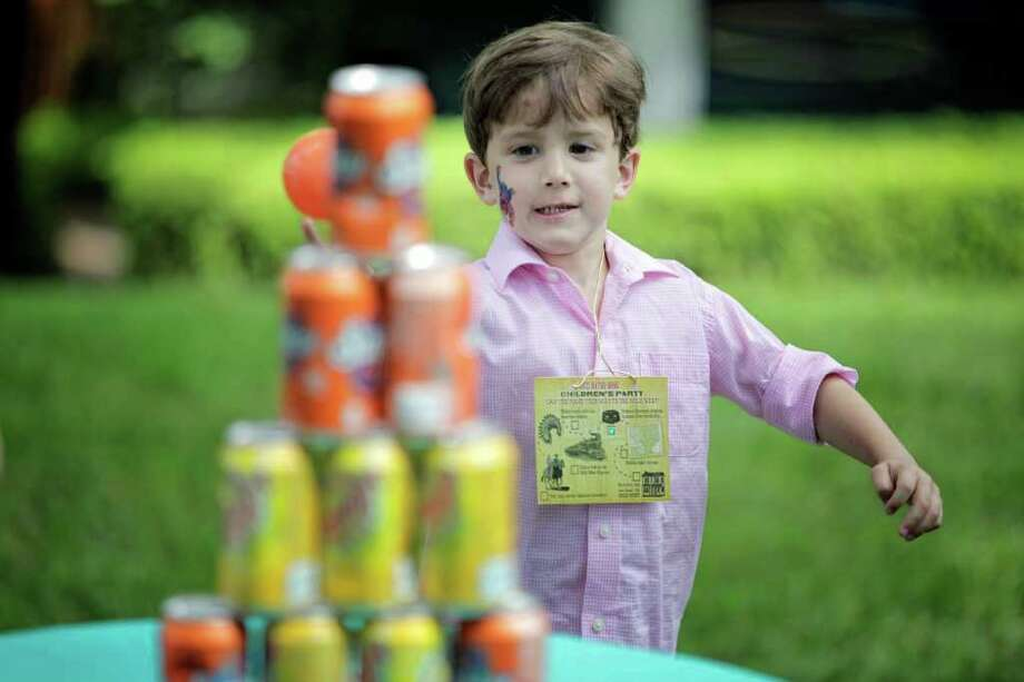 4-year-old Peter Liuzzi attempts to knock down a tower of cans during the Bayou Bend children's party. Photo: TODD SPOTH / TODD SPOTH, 2012