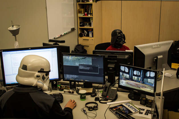 "Microsoft employees Pedro Perez and Jon Williams don Stormtrooper and Darth Vader helmets while ""working."" Photo: Microsoft"