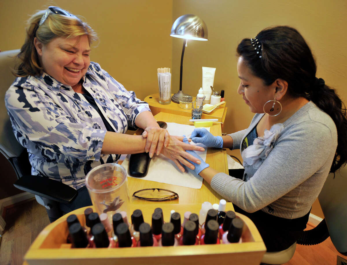 Karen Loker, left, of Redding, gets a manicure by esthetician Sandra Yupangui at Escape Salon & Spa in Bethel on Tuesday, April 3, 2012. Escape Salon & Spa is celebrating its 25th year in business.