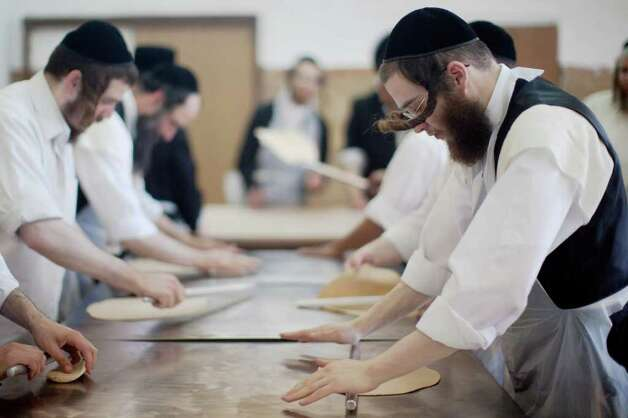 TEL AVIV, ISRAEL - APRIL 03:  (ISRAEL OUT)  Ultra-Orthodox Jewish men prepare the Matzoth or unleavened bread on April 3, 2012 in Bnei Brak, Israel. Religious Jews throughout the world eat matzoth during the eight-day Pesach holiday (Passover), which begins the April 6, with the sunset to commemorate the Israelis' exodus from Egypt some 3,500 years ago and commemorate their ancestors' plight by refraining from eating leavened food products. Photo: Uriel Sinai, Getty Images / 2012 Getty Images