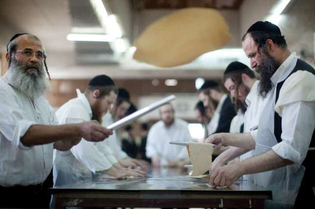 BNEI BRAK, ISRAEL - APRIL 03:  (ISRAEL OUT)  Ultra-Orthodox Jewish men prepare the Matzoth or unleavened bread on April 3, 2012 in Bnei Brak, Israel. Religious Jews throughout the world eat matzoth during the eight-day Passover, or Pesach, holiday, which begins the April 6, at sunset.  The Jewish holiday commemorates the Israelis' exodus from Egypt some 3,500 years ago and their ancestors' plight by refraining from eating leavened food. . Photo: Uriel Sinai, Getty Images / 2012 Getty Images