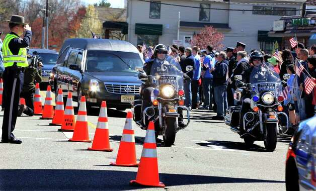 Motorcycle police lead a hearse carrying the remains of Marine Staff Sgt. Joseph D'Augustine, who was killed last week while serving in Afghanistan, past hundreds of Waldwick, N.J., residents lined up along the streets to honor him Tuesday, April 3, 2012. The 29-year-old died March 27 in the Helmand province, nearly two weeks before he was due to come home for his sister's wedding. D'Augustine graduated from Waldwick High School in 2001. D'Augustine was assigned to an explosive ordnance disposal unit from the 8th Engineer Support Battalion of the 2nd Marine Logistics Group, part of the Second Marine Expeditionary Force at Camp Lejeune, N.C. Photo: AP