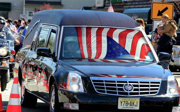 A hearse carrying the remains of Marine Staff Sgt. Joseph D'Augustine, who was killed last week while serving in Afghanistan, passes hundreds of Waldwick, N.J., residents lined up along the streets to honor him Tuesday, April 3, 2012. The procession passed under an American flag held aloft by two fire department ladder trucks. The 29-year-old died March 27 in the Helmand province, nearly two weeks before he was due to come home for his sister's wedding. D'Augustine graduated from Waldwick High School in 2001. D'Augustine was assigned to an explosive ordnance disposal unit from the 8th Engineer Support Battalion of the 2nd Marine Logistics Group, part of the Second Marine Expeditionary Force at Camp Lejeune, N.C. Photo: AP