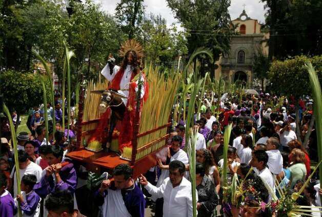 People carry a statue of Jesus Christ during a Palm Sunday procession in Mexico City, Sunday April 1, 2012. Palm Sunday commemorates Jesus Christ's triumphant entry into Jerusalem and marks the start of the Christian Holy Week. Photo: AP