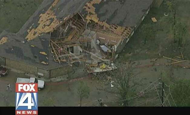 This frame grab provided by KDFW-TV shows storm damage Tuesday in  Arlington, Texas.  Several reported tornadoes tore through the Dallas area on Tuesday, tossing semis in the air and leaving crumpled tractor trailers strewn along highways and in truck stop parking lots. (AP Photo/KDFW-TV) Photo: AP