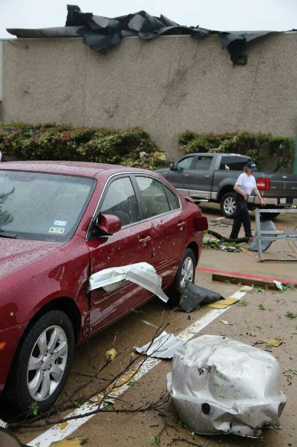 "A car is damaged after a storm passed through in Arlington, Texas on Tuesday, April 3, 2012.  Tornadoes tore through the Dallas area on Tuesday, tearing roofs off homes, tossing trucks into the air and leaving flattened tractor trailers strewn along highways and parking lots. The National Weather Service confirmed at least two separate ""large and extremely dangerous"" tornadoes in the Dallas-Fort Worth area. Several other developing twisters were reported as a band of violent storms moved north through the metropolitan area.   (AP Photo/The Dallas Morning News, Nathan Hunsinger )  MANDATORY CREDIT; MAGS OUT; TV OUT; INTERNET OUT; AP MEMBERS ONLY Photo: Nathan Hunsinger, Associated Press / Nathan Hunsinger/The Dallas Morning News"
