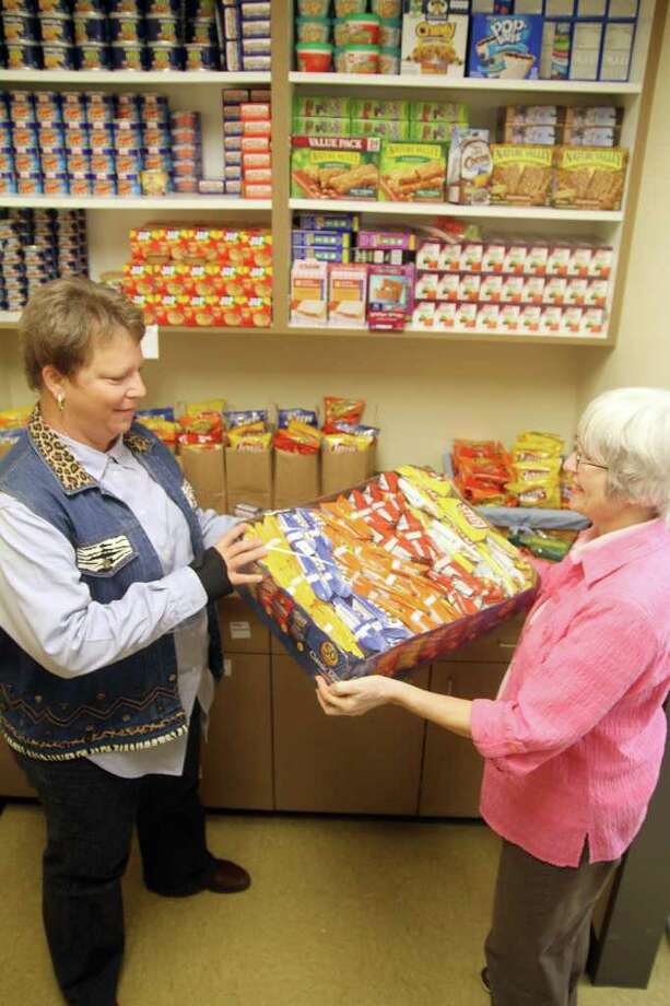 Julie Laverell, director of the Society of St. Stephen Outreach Ministry, and Lois Dunlap stock the pantry. Photo: Pin Lim / Copyright Pin Lim.