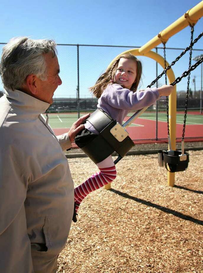 Dave Hartford gives granddaughter Lily Grigas, 4, both of Milford, a push on the swings at Fowler Field in downtown Milford on Tuesday, April 3, 2012. Photo: Brian A. Pounds / Connecticut Post