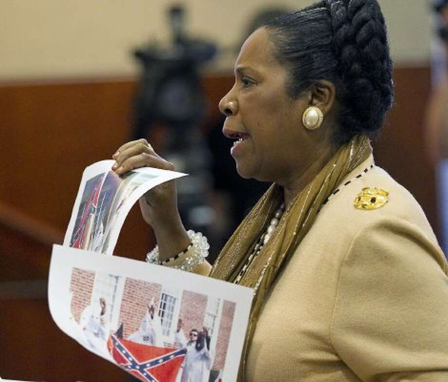 Rep. Sheila Jackson Lee holds photographs on Nov. 10, 2011, in Austin. Texas drivers won't be able to put Confederate license plates on their vehicles after a state board unanimously rejected the proposed design. (Ralph Barrera / The Associated Press)