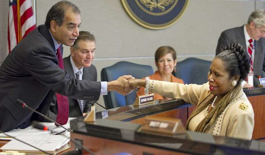 Rep. Sheila Jackson Lee congratulates Dept. of Motor Vehicles Board member Raymond Palacios after the board voted against the Confederate license plates, Nov. 10, 2011, in Austin. (Ralph Barrera / The Associated Press)