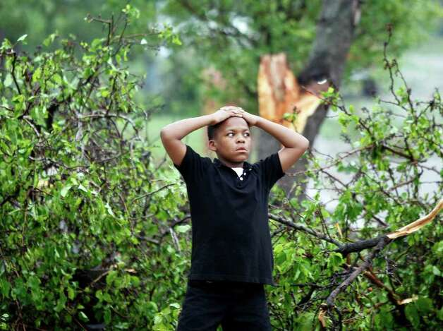 "Ten year-old Ty Proctor surveys damage after a tornado struck  Arlington, Texas, on Tuesday.  Several reported tornadoes tore through the Dallas area on Tuesday, tossing semis in the air and leaving crumpled tractor trailers strewn along highways and in truck stop parking lots.   The National Weather Service reported at least two separate ""large and extremely dangerous"" tornadoes south of Dallas and Fort Worth.  (AP Photo/The Fort Worth Star-Telegram, Ron Jenkins) Photo: AP"