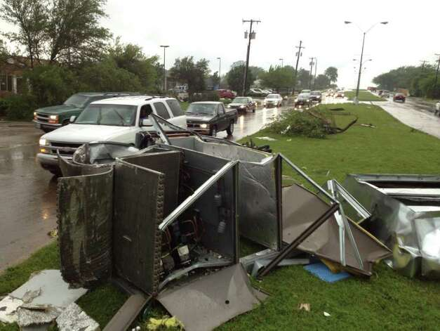 "Debris scatter the street in southern Dallas County, Texas  on Tuesday.  Several reported tornadoes tore through the Dallas area on Tuesday, tossing semis in the air and leaving crumpled tractor trailers strewn along highways and in truck stop parking lots.   The National Weather Service reported at least two separate ""large and extremely dangerous"" tornadoes south of Dallas and Fort Worth. Photo: AP"