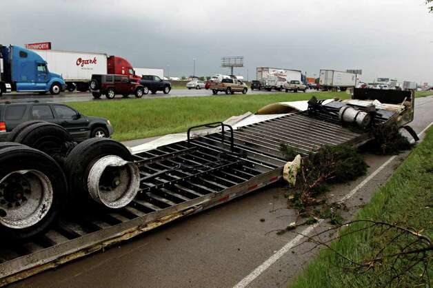 "A flattened trailer lays along the frontage road of Interstate 20 after a tornado reportedly tore through the southeastern portion of Dallas County on Tuesday near Lancaster, Texas. The National Weather Service confirmed at least two separate ""large and extremely dangerous"" tornadoes in the Dallas-Fort Worth area. Several other developing twisters were reported as a band of violent storms moved north through the metropolitan area. Officials had no immediate information about injuries. Photo: AP"