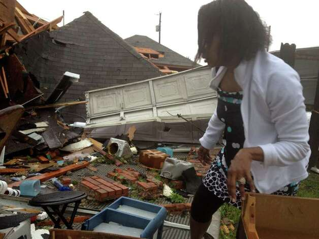 "Jerica Jenkins surveys damage to her home after it was hit by a tornado Tuesday in Lancaster, Texas.  The National Weather Service confirmed at least two separate ""large and extremely dangerous"" tornadoes in the Dallas area. Photo: AP"