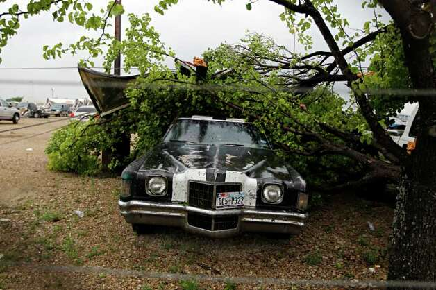 "A downed tree lays on top of a parked car after a tornado reportedly tore through the southeastern portion of Dallas County on Tuesday near Lancaster, Texas. The National Weather Service confirmed at least two separate ""large and extremely dangerous"" tornadoes in the Dallas-Fort Worth area. Several other developing twisters were reported as a band of violent storms moved north through the metropolitan area. Officials had no immediate information about injuries. Photo: AP"