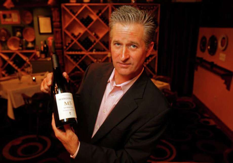 Mockingbird Bistro's wine steward Keith Thompson poses for a portrait with a bottle of Magerum M5, Rhone style blend wine Thursday, March 8, 2012, in Houston. ( James Nielsen / Chronicle ) Photo: James Nielsen / © 2011 Houston Chronicle