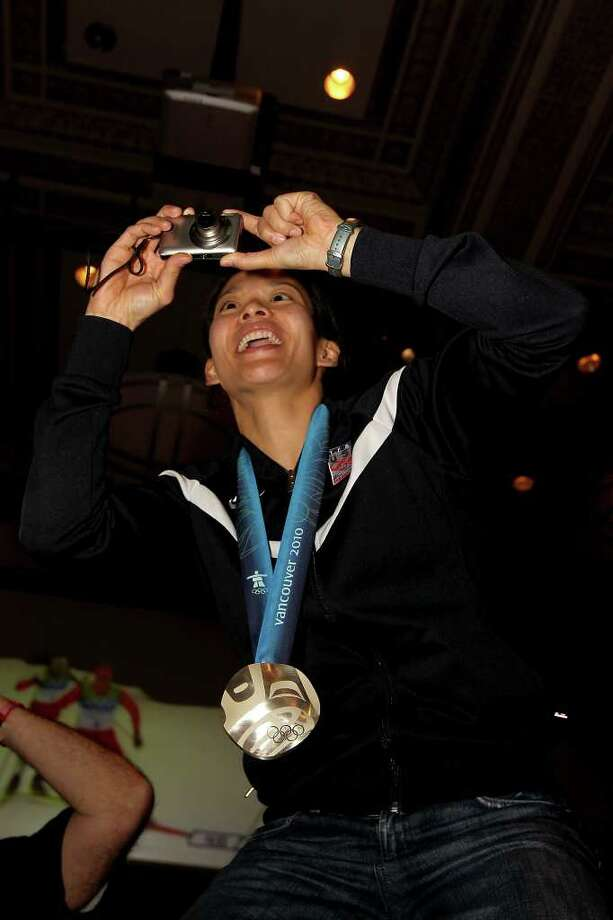 VANCOUVER, BC - FEBRUARY 25:  Hockey player Julie Chu of the United States takes a picture as she wears her silver medal at the P&G Family Home on Februiary 25, 2010 during the Olympic Winter Games in Vancouver, Canada.  (Photo by Christian Petersen/Getty Images for P&G) Photo: Christian Petersen, ST / 2010 Getty Images