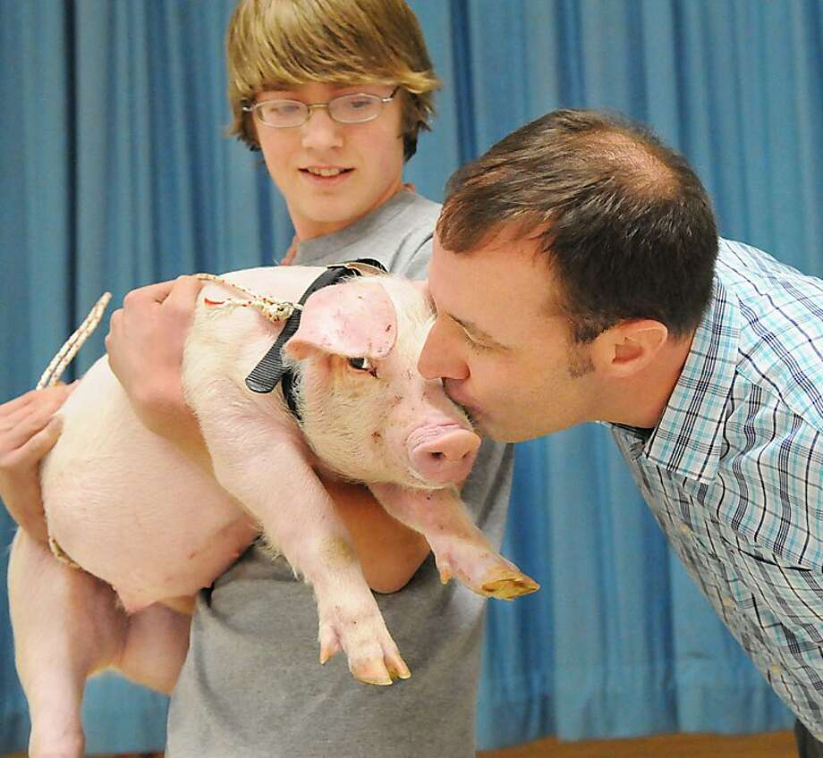 Principal James Hale kisses a pig during an assembly at Forge Road Elementary School in Palmyra, Penn., on Friday, March 30 2012. Hale challenged the students to read 3,000 books during the month in March for Read Across America, and if they met this challenge he would kiss a pig. Holding the pig is Michael Knauer. (AP Photo/Lebanon Daily News, Ashley Walter)  THE PATRIOT-NEWS OUT Photo: Ashley Walter, Associated Press