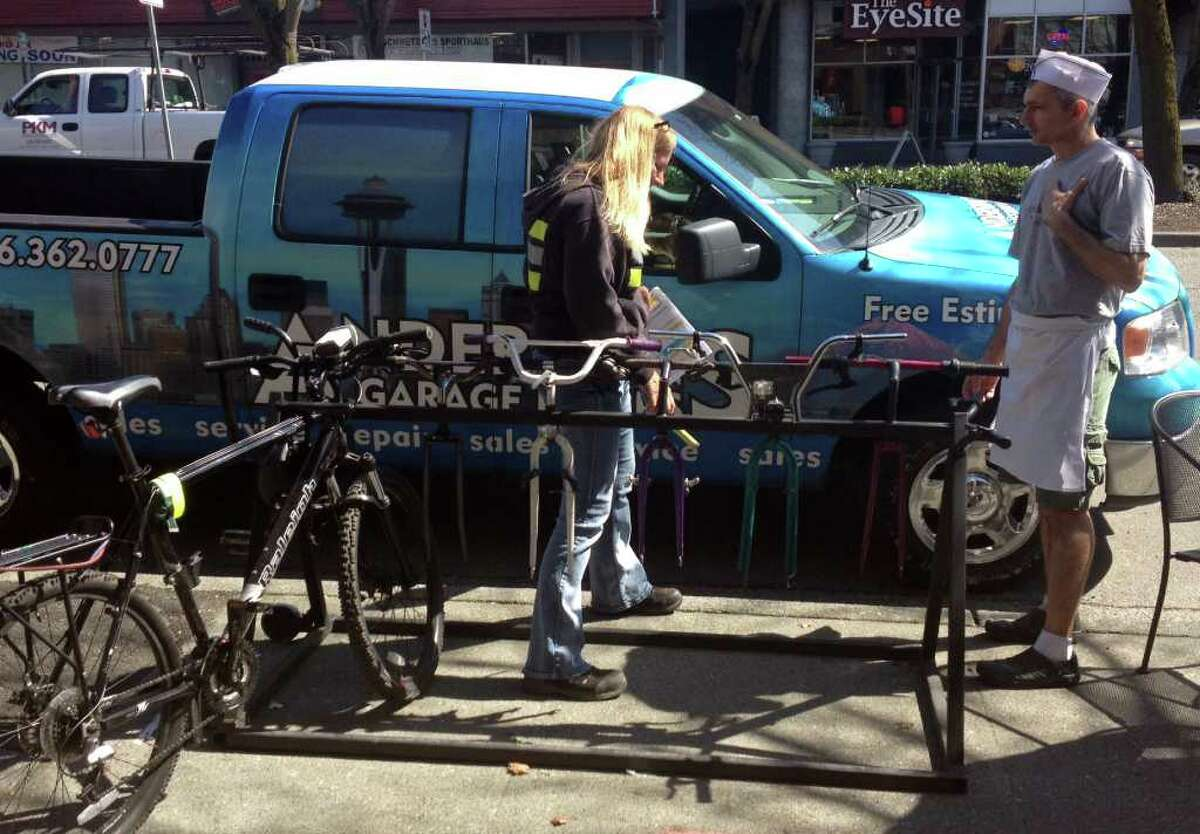 A city employee talks with Kaffeeklatsch co-owner Brian Hensley April 2 about the Lake City coffee shop's removable bike rack. The city wants that one moved because it's not up to code so the city can install a permanent bike rack.