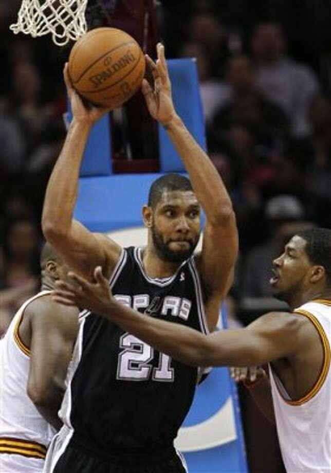 San Antonio Spurs' Tim Duncan (21) clears out a rebound between Cleveland Cavaliers' Antawn Jamison, left, and Tristan Thompson, right, during the second half of an NBA basketball game in Cleveland on Tuesday, April 3, 2012.  (AP Photo/Amy Sancetta) (AP)