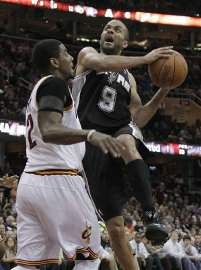 San Antonio Spurs' Tony Parker (9) drives to the basket against Cleveland Cavaliers' Kyrie Irving (2) during the first half of an NBA basketball game in Cleveland on Tuesday, April 3, 2012. (AP Photo/Amy Sancetta) (AP)