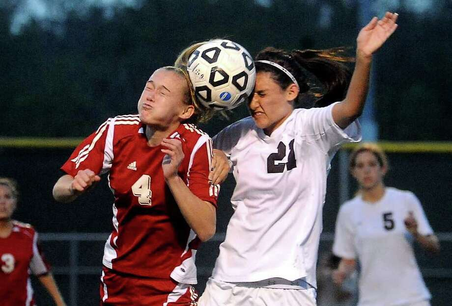 Lumberton's Macy Mitchell and Magnolia's Reagen Wiley header the ball at Kingwood Park High School in Kingwood, Tuesday, April 3, 2012. Tammy McKinley/The Enterprise Photo: TAMMY MCKINLEY