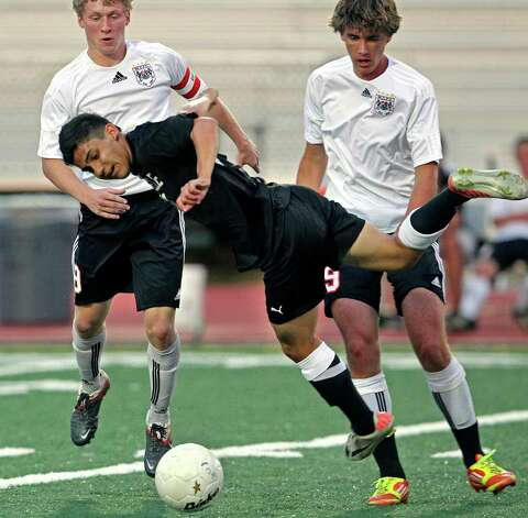 Steele's Miguel Sandoval twists in the air after being fouled by Colton Wilson (right) as Charger teammate Zach Berger watchers as Churchill plays Steele in boys and girls playoff soccer at Comalander Stadium on  April 3, 2012.  Tom Reel/ San Antonio Express-News Photo: TOM REEL, Express-News / San Antonio Express-News