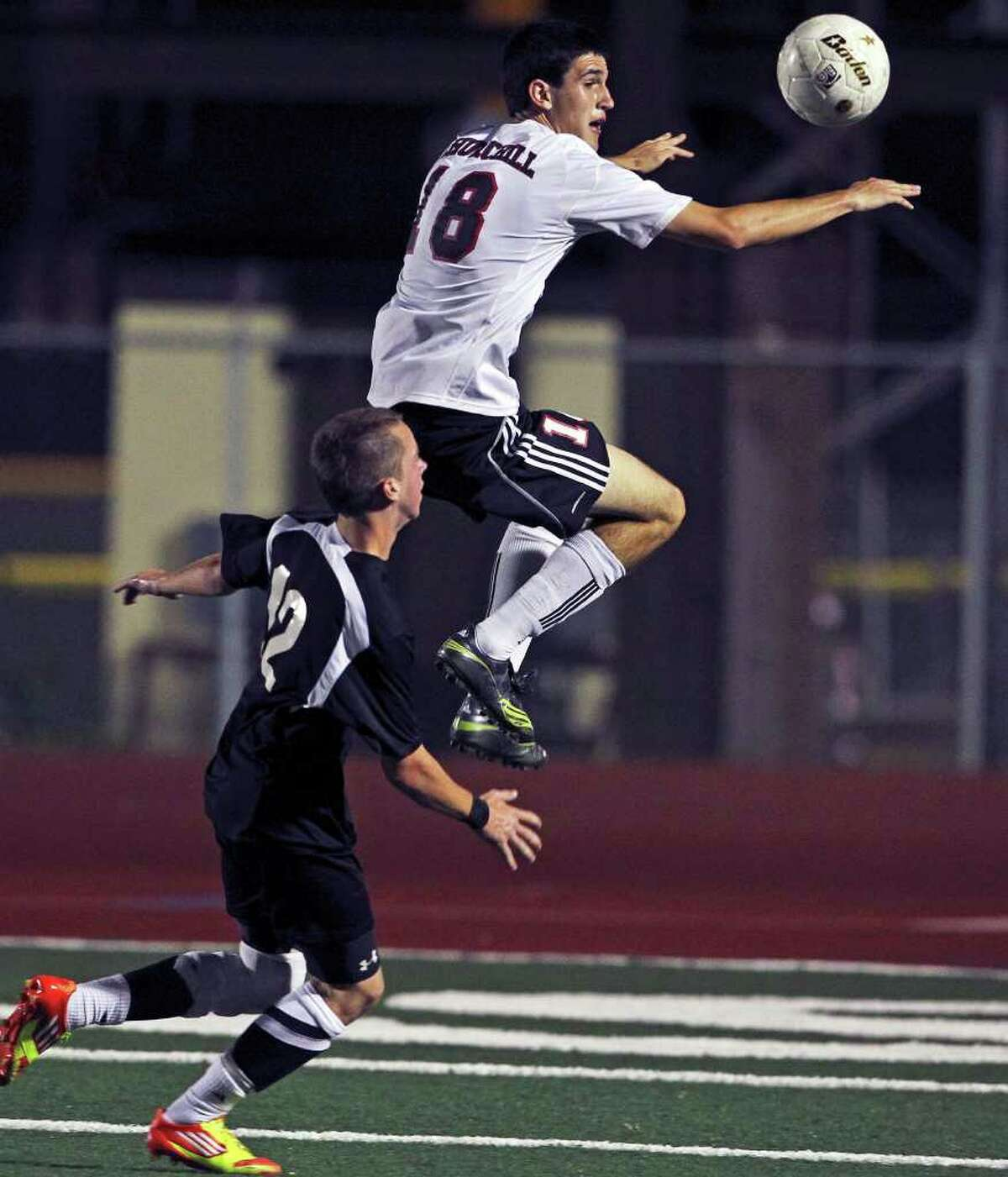 Churchill's Brandon Severyn leaps to control in front of Steele's Austin Schlather (12) as Churchill plays Steele in boys and girls playoff soccer at Comalander Stadium on April 3, 2012. Tom Reel/ San Antonio Express-News