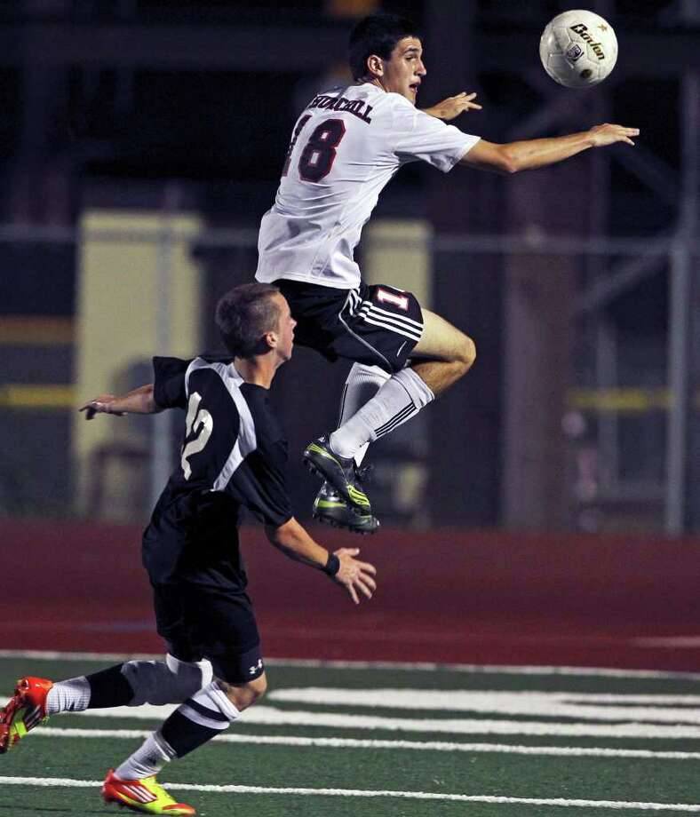Churchill's Brandon Severyn leaps to control in front of Steele's Austin Schlather (12) as Churchill plays Steele in boys and girls playoff soccer at Comalander Stadium on  April 3, 2012.  Tom Reel/ San Antonio Express-News Photo: TOM REEL, Express-News / San Antonio Express-News