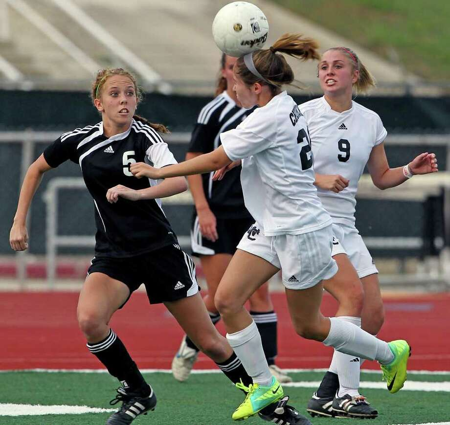 Churchill's Krystel Wolfe heads the ball away from  Steele's Kayla Nagle (5) as Charger teammate Lauren Peck watches as Churchill plays Steele in boys and girls playoff soccer at Comalander Stadium on  April 3, 2012.  Tom Reel/ San Antonio Express-News Photo: TOM REEL, Express-News / San Antonio Express-News