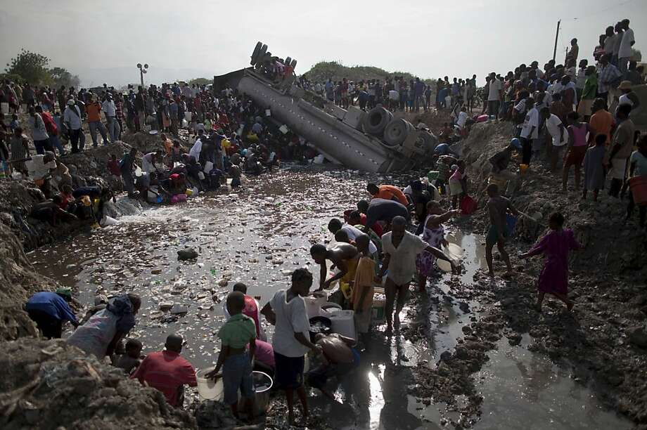 People collect fuel mixed with water from a canal after an accident involving a truck carrying diesel fuel in the neighborhood of Cite Soleil, Port-au-Prince, Haiti, Tuesday, April 3, 2012. The scramble for the gas is understandable in Haiti: fuel stations charge as much as $5 a gallon in a country where the bulk of its 10 million people earns about $2 a day. (AP Photo/Ramon Espinosa) Photo: Ramon Espinosa, Associated Press