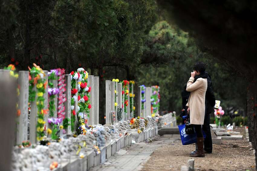 In a photograph taken on April 3, 2012, a Chinese family pray at the tomb of a family member during the annual