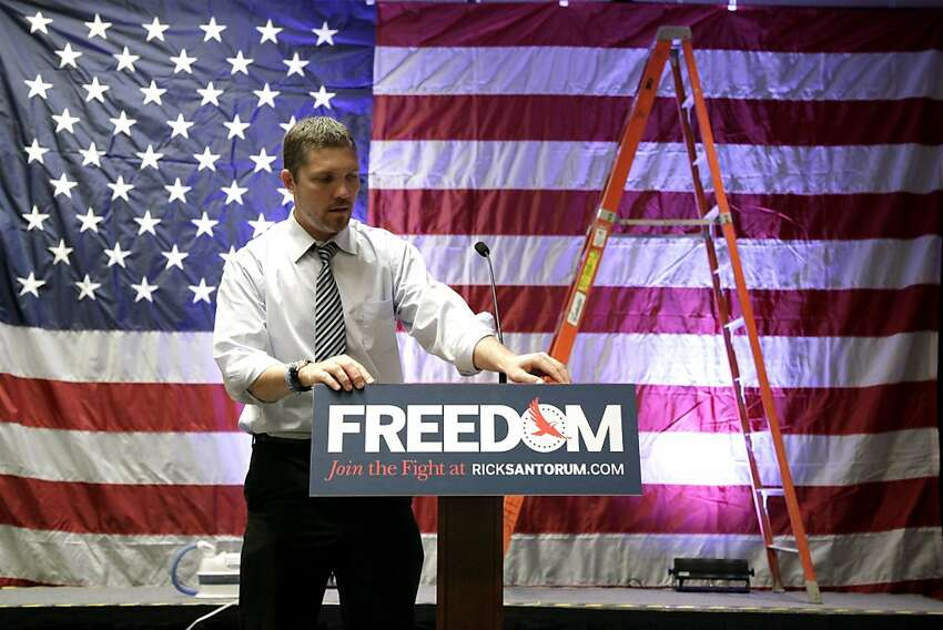 Clint Vanwuffen, a campaign aide for Republican presidential candidate, former Pennsylvania Sen. Rick Santorum, hangs a sign on the podium as campaign workers get ready for the election night party in Cranberry, Pa., Tuesday, April 3, 2012. (AP Photo/Jae C. Hong)